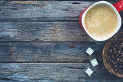 Cuenco de granos de café asados, de taza de café roja y de cubos del azúcar fotos de archivo