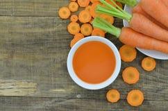 Cuenco de jugo de zanahoria con las rebanadas en fondo de madera Imágenes de archivo libres de regalías