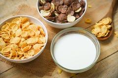 Cuenco de los copos de maíz del desayuno y de diversos cereales y taza de la leche en el fondo de madera para la comida sana del fotos de archivo libres de regalías