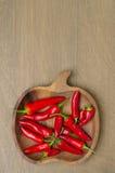 Cuenco de madera con la opinión superior roja de las pimientas de chile (y espacio para el texto) Foto de archivo libre de regalías