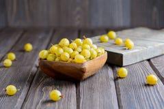 Cuenco de madera de amarillo maduro de la grosella espinosa imágenes de archivo libres de regalías