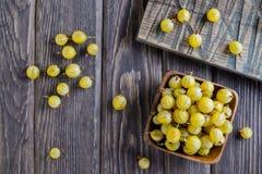 Cuenco de madera de amarillo maduro de la grosella espinosa foto de archivo
