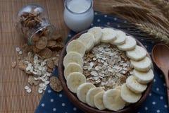 Cuenco de madera de copos de maíz y de harina de avena orgánicos con el plátano Desayuno nutritivo, ingredientes alimentarios cru Imagen de archivo