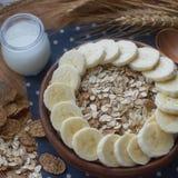 Cuenco de madera de copos de maíz y de harina de avena orgánicos con el plátano Desayuno nutritivo, ingredientes alimentarios cru Fotografía de archivo