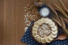 Cuenco de madera de copos de maíz y de harina de avena orgánicos con el plátano Desayuno nutritivo, ingredientes alimentarios cru Fotografía de archivo libre de regalías