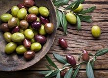 Cuenco de madera por completo de aceitunas y de ramitas verdes olivas imagenes de archivo