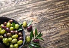 Cuenco de madera por completo de aceitunas y de ramitas verdes olivas imagen de archivo libre de regalías