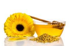 Cuenco de miel cerca de una pila de polen y de flor Fotografía de archivo