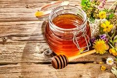 Cuenco de miel con el cazo al lado del manojo de flores Imagenes de archivo