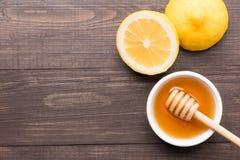 Cuenco de miel y de limones dulces en la tabla de madera Imagen de archivo
