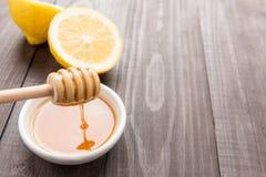 Cuenco de miel y de limones dulces en la tabla de madera Foto de archivo libre de regalías