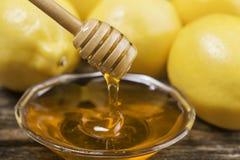 Cuenco de miel y de limones dulces en la tabla de madera Fotos de archivo