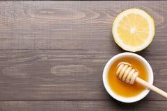 Cuenco de miel y de limones dulces en la tabla de madera Fotos de archivo libres de regalías