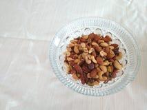 Cuenco de nueces mezcladas en un mantel blanco llano foto de archivo