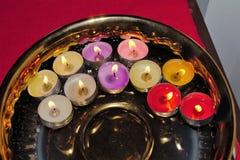 Cuenco de oro con la flotación de velas coloridas de la luz del té Fotos de archivo