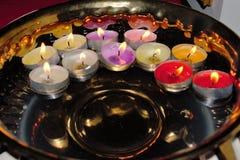 Cuenco de oro con la flotación de velas coloridas de la luz del té Fotografía de archivo libre de regalías