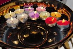 Cuenco de oro con la flotación de velas coloridas de la luz del té Foto de archivo