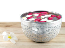 Cuenco de plata con los pétalos de la flor que flotan en la superficie Imágenes de archivo libres de regalías
