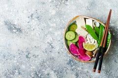 Cuenco de sopa asiático de tallarines del udon del vegano con el jengibre y las setas caldo, queso de soja, guisantes rápidos, ca Foto de archivo libre de regalías