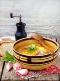 Cuenco de sopa con las patatas, las zanahorias, las pimientas dulces y los tomates en un fondo de madera Imagen de archivo libre de regalías