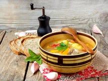 Cuenco de sopa con las patatas, las zanahorias, las pimientas dulces y los tomates en un fondo de madera Fotografía de archivo libre de regalías