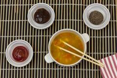 Cuenco de sopa de verduras con los palillos en una estera de bambú de la porción Imágenes de archivo libres de regalías
