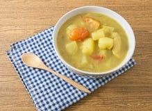 Cuenco de sopa del curry con la patata y el tomate Imagenes de archivo