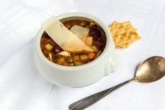Cuenco de sopa del minestrone con parmesano cortado en el fondo blanco fotografía de archivo