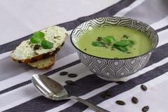 Cuenco de sopa de la crema del bróculi, de pan del grano con las semillas de calabaza y de cuchara en la tabla, concepto vegetari imagen de archivo