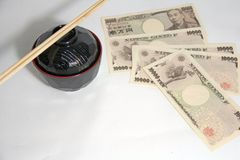 Cuenco de sopa rojo de Miso del borde del color negro y palillos de madera con los billetes de banco de los yenes de Japón en el  imagen de archivo