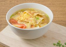 Cuenco de sopa tailandesa de la tortilla con los tomates y la cebolleta foto de archivo