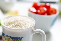 cuenco de tomates de cereza y de una taza de arroz Foto de archivo libre de regalías