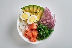 cuenco del empuje con los salmones, aguacate, arroz, ensalada de Chuka, cebollas dulces, huevos de codornices asperjados con el s foto de archivo libre de regalías
