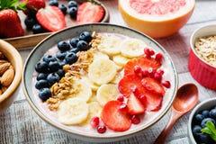 Cuenco del smoothie de Acai con el plátano, la fresa, el arándano y el granola Imagen de archivo