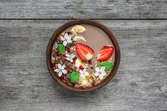Cuenco del smoothie de la proteína del plátano del cacao con el granola del chocolate, la fresa y las semillas de la granada ador Imágenes de archivo libres de regalías