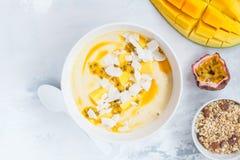 Cuenco del smoothie del mango con el coco y la fruta de la pasión imagen de archivo