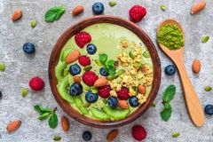 Cuenco del smoothie del té verde de Matcha con las frutas frescas, las bayas, las nueces, las semillas y el granola con una cucha foto de archivo libre de regalías