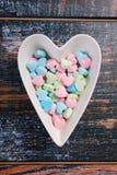Cuenco en forma de corazón con los caramelos de azúcar coloridos para las tarjetas del día de San Valentín Fotos de archivo