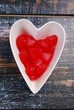 Cuenco en forma de corazón con los caramelos rojos para las tarjetas del día de San Valentín Fotos de archivo
