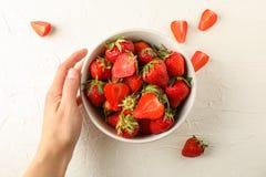 Cuenco femenino del control de la mano con las fresas frescas en el fondo blanco, espacio para el texto Frutas del dulce de veran imagen de archivo