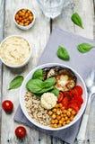 Cuenco mediterráneo del hummus de la quinoa con las berenjenas, los tomates y el SP Imagen de archivo