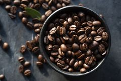 Cuenco negro con los granos de café dispersados en la luz oscura de la ventana de la opinión de top del fondo de la tabla imagen de archivo