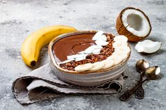 Cuenco sano del desayuno El cuenco del smoothie del plátano del chocolate con el coco forma escamas, granola, rebanadas del pláta Imagen de archivo