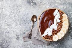 Cuenco sano del desayuno El cuenco del smoothie del plátano del chocolate con el coco forma escamas, granola, rebanadas del pláta Foto de archivo