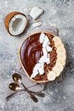 Cuenco sano del desayuno El cuenco del smoothie del plátano del chocolate con el coco forma escamas, granola, rebanadas del pláta Fotografía de archivo