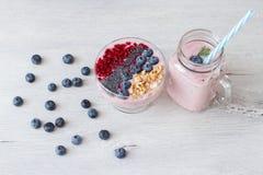 Cuenco sano del desayuno: smoothie del arándano con el plátano, frambuesa, zarzamora, nueces en la tabla imagenes de archivo