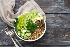 Cuenco verde de Buda con las lentejas, la quinoa, el aguacate, el pepino, la lechuga fresca, hierbas y semillas Imagen de archivo