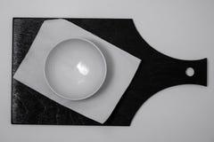 Cuenco y servilleta blancos en tablero negro imagen de archivo
