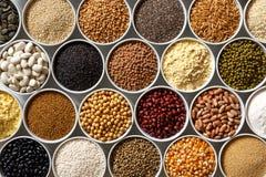 Cuencos blancos dispuestos con pulsos crudos, granos y semillas en w Imagen de archivo libre de regalías