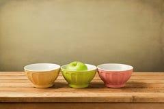Cuencos coloridos con la manzana verde Imagenes de archivo
